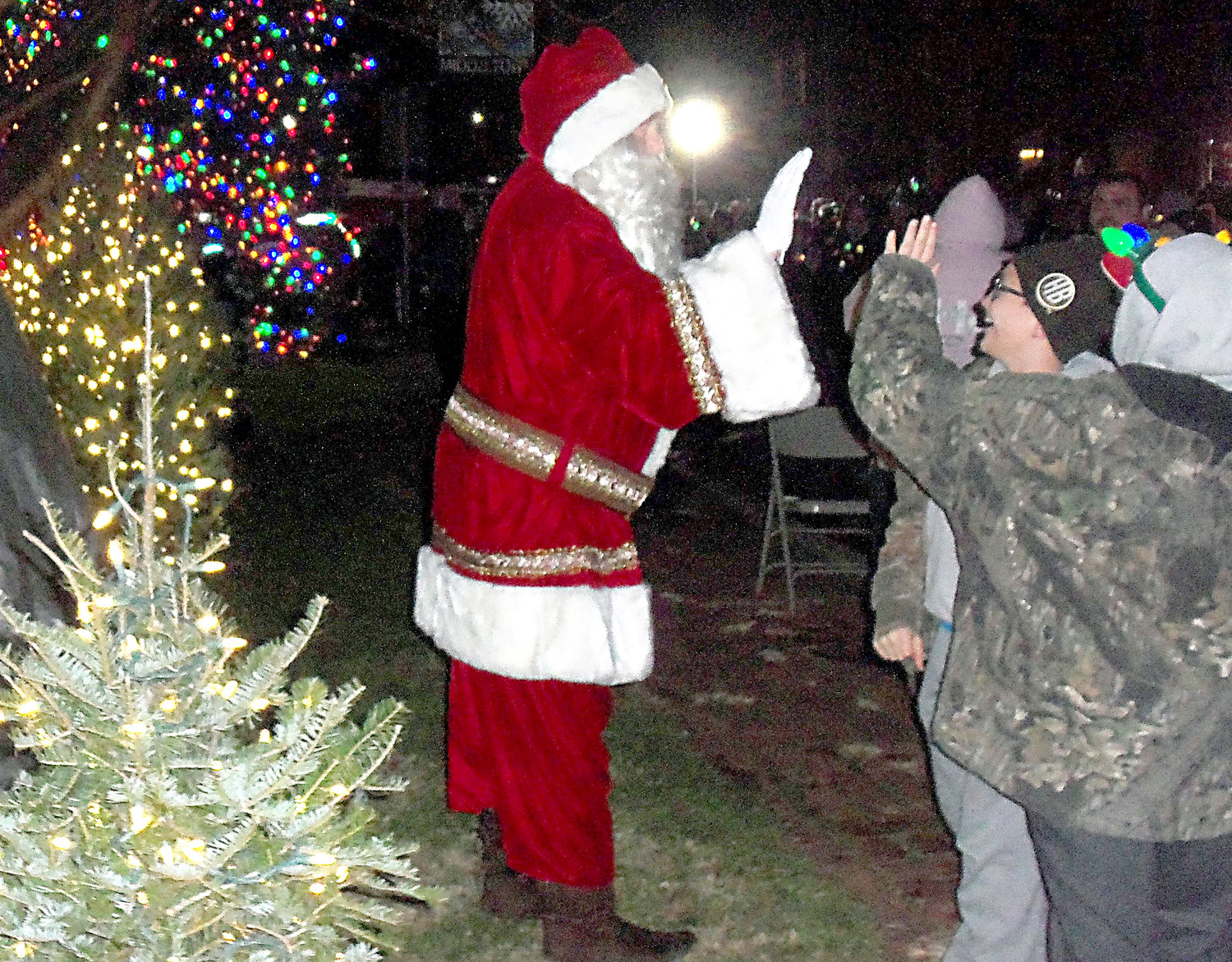 Santa Claus gives a high-five to young fans outside of Middletown's new Santa house on Saturday night, Nov. 30, during the borough's tree-lighting ceremony..