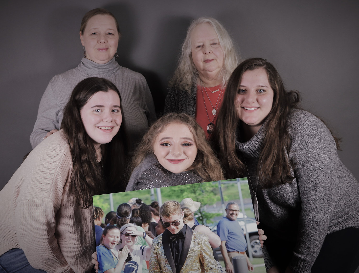 Heather Bernola and Torin's maternal grandmother, Linda Nelson, rear, pose with Heather's three daughters and Torin's biological sisters, Quinn Dworchak, Kelsey Dworchak and Mikala Dworchak. They are holding a picture of Torin from the Middletown Area High School prom in 2019.
