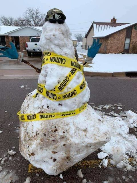 Hunter Russell built a snowman in the middle of 15th Street to warn motorists of icy spots in the road and to slow down.