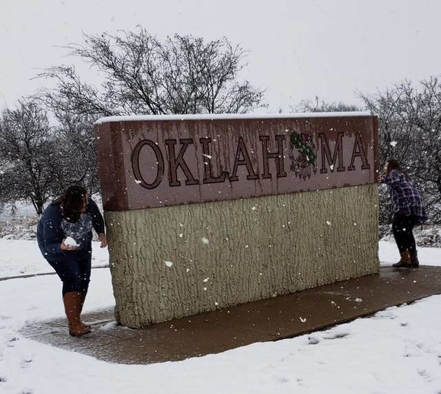 Brittany Olsen chases her daughter, Karli Olsen, 11, around the Oklahoma sign during their first snowball fight of 2019.