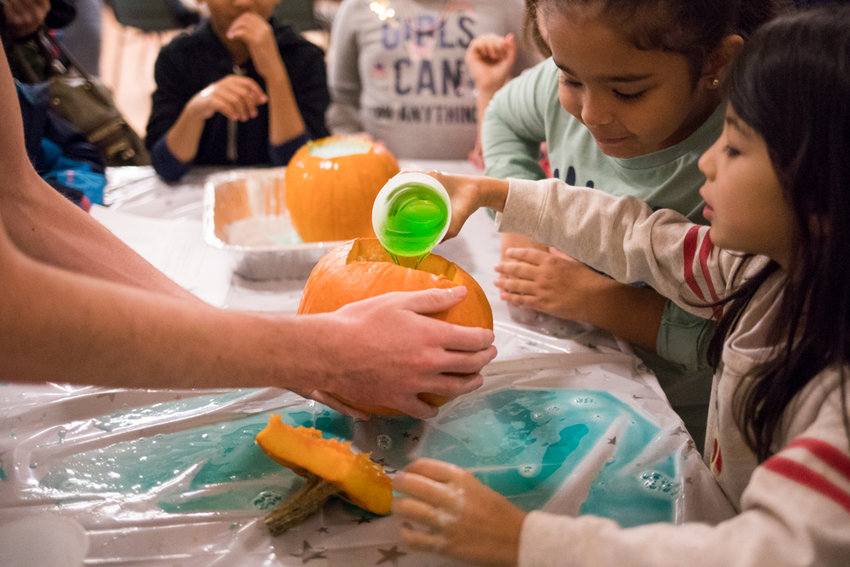 P.S. 24 students take turns pouring dish soap into a pumpkin filled with baking soda at Manhattan College during STEM Junior Day. Once vinegar is added, the concoction would explode. This is the National Society of Black Engineers' second STEM Junior Day where their goal is to instill an appreciation for science within children.