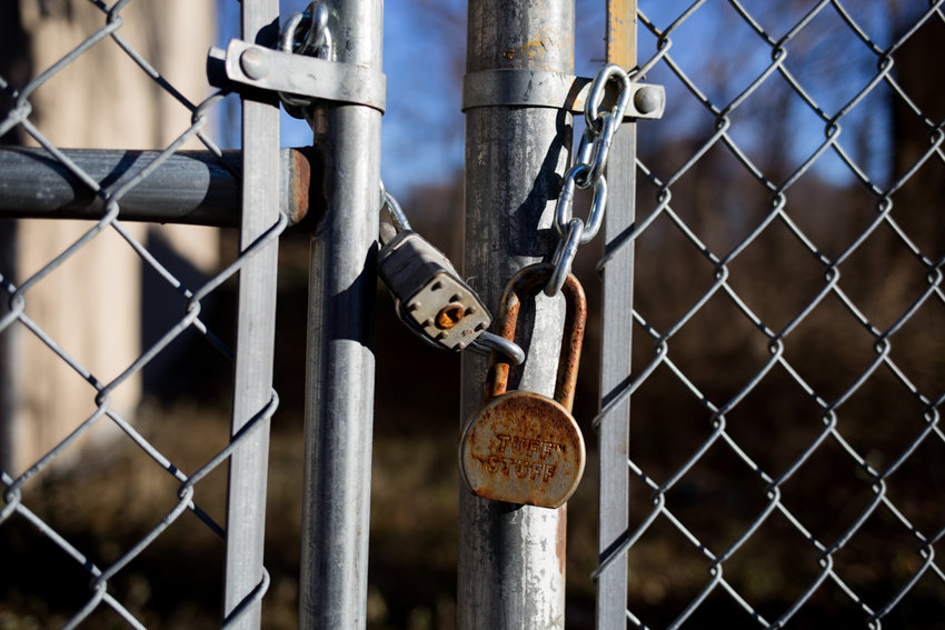 Two padlocks secure an iron fence around a vacant lot at 5278 Post Road. The owner of the property filed a variance request to construct a mixed-use nine-story building that otherwise would exceed zoning requirements for the area. Councilman Andrew Cohen opposes the request, saying it would change the character of the neighborhood.
