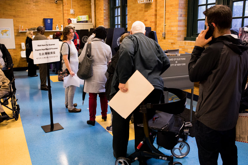 People wait in line for the two functioning ballot scanners at P.S. 81 on Nov. 6. With New York suffering under some of the most restrictive voting laws in the United States, Gov. Andrew Cuomo says he wants to revamp the state's maddening system, calling for automatic voter registration, easing voting-by-mail restrictions, and expanding the number of days to vote.