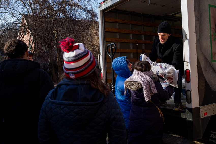 Matt Abrams Gerber, chief operating officer of The Riverdale Y, hands a bag of rice to volunteers that will later be packed and donated for a day of service to commemorate Martin Luther King Jr.