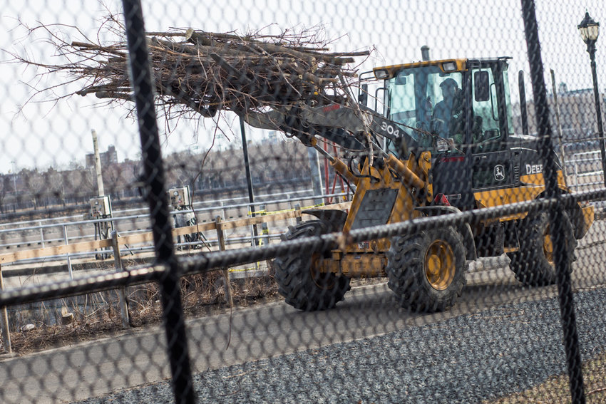 A wheel loader carries tree branches toward a dumpster along the Jerome Park Reservoir, the area east of Kingsbridge undergoing a $15 million upgrade from the city's environmental protection department.