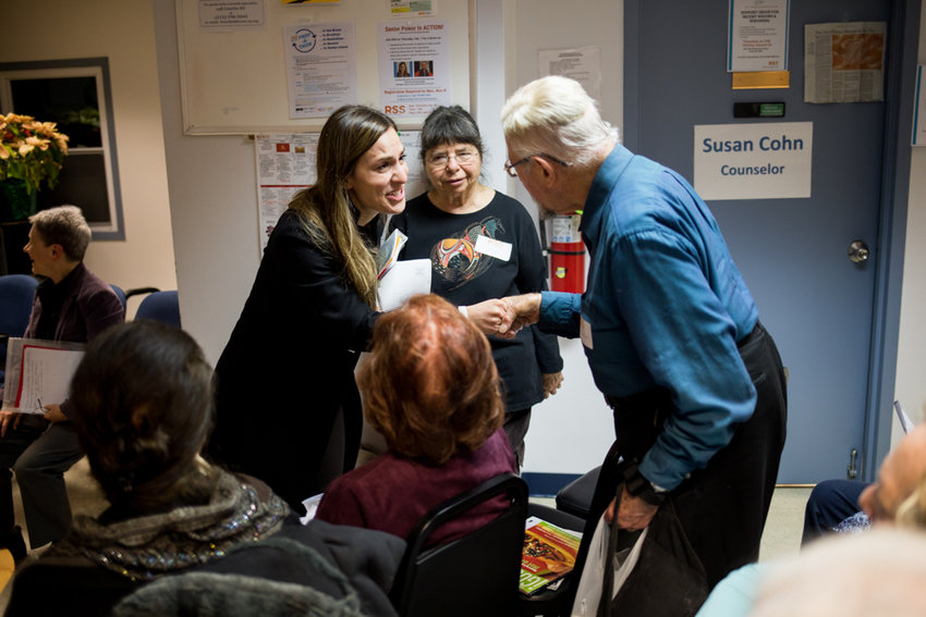 State Sen. Alessandra Biaggi speaks with Marvin Goodman ahead of an information session about the New York Health Act at RSS-Riverdale Senior Services.