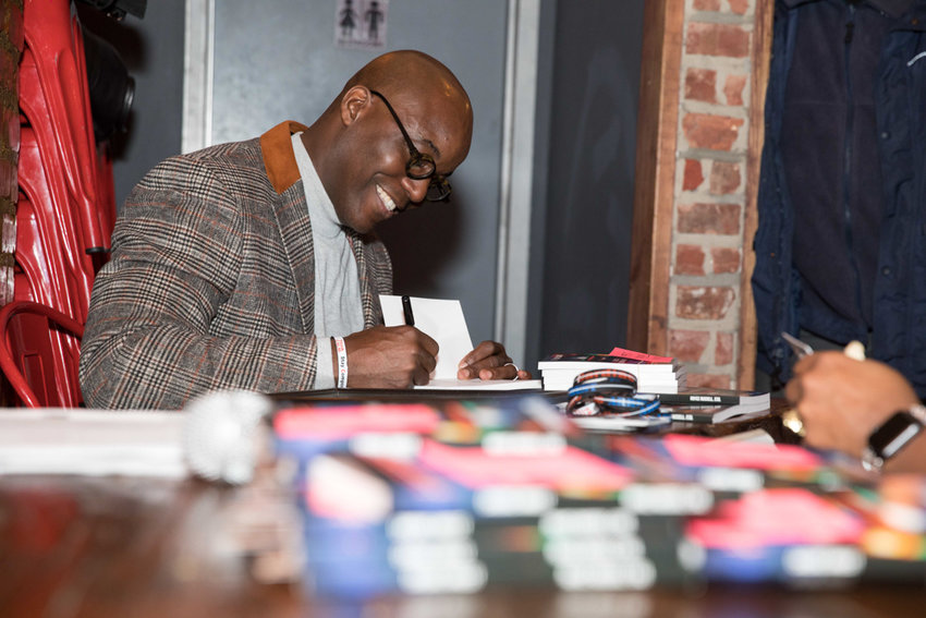 Royce Russell, a civil rights and immigration lawyer, signs a copy of his book 'Cardiac Arrest' at a launch party at the Bronx Draft House last December. The book details how to handle interactions with police.
