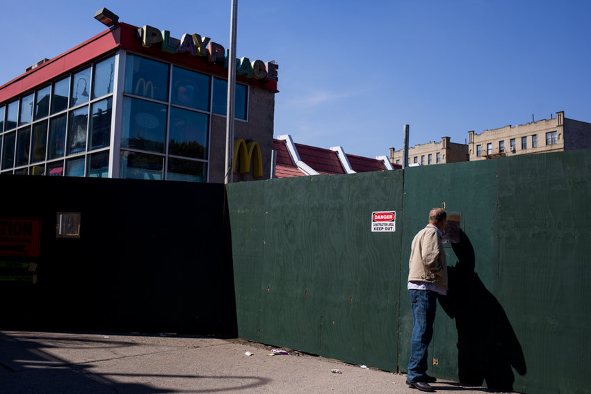 A pedestrian takes a peek through a hole in a construction barrier surrounding the McDonald's at 5765 Broadway where a giant pit has become the source of much speculation. But owner Chris Trefz assures nugget-craving locals won't have to wait longer than a few more months to get their fix, with reopening scheduled for July.