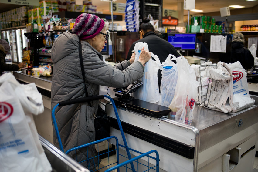 A customer collects her groceries in Key Food on Riverdale Avenue. As part of the state's new budget, lawmakers approved a ban on single-use plastic bags, part of an unusual power the governor has to enact policy through the budget process.