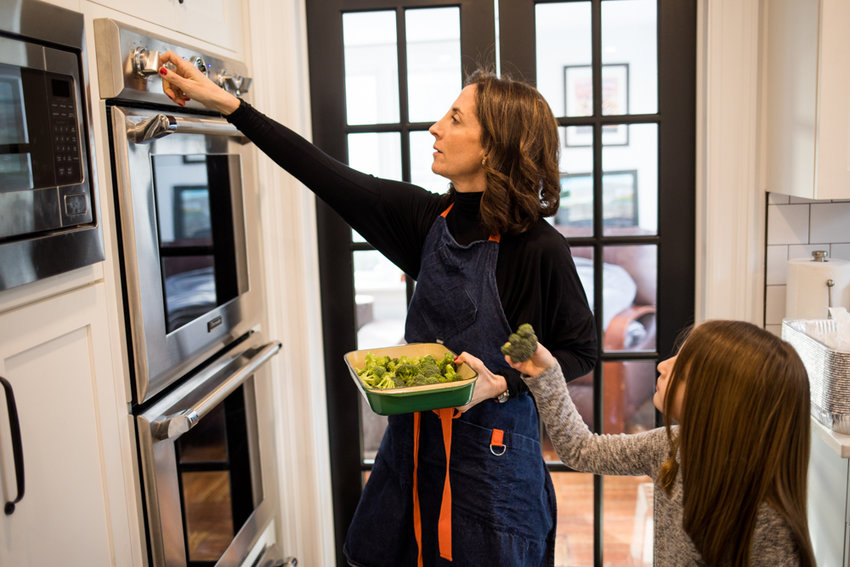 Lea Geller checks the temperature on the oven while her daughter Sidney picks up a piece of broccoli. Geller balances a part-time teaching schedule, the demands of five children and her writing. Her debut novel, 'Trophy Life,' was published April 9.