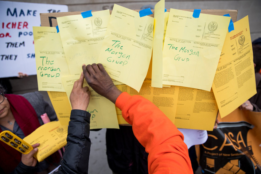 Protesters paste up mock eviction notices for landlords dubbed the borough's 'worst evictors' by tenants rights groups during a rally outside the Bronx Housing Civil Court on Grand Concourse.