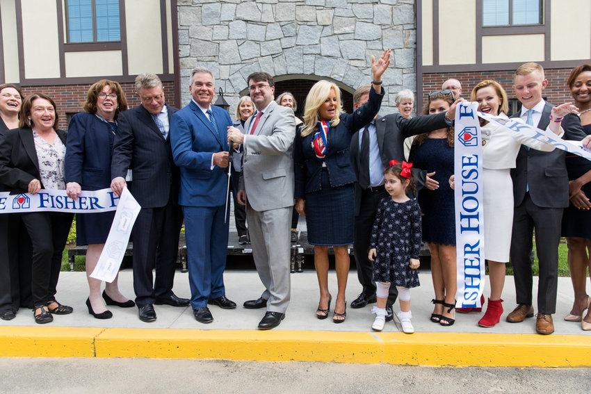 People cheer after cutting the ribbon to mark the opening of the Fisher Houses, a living facility for veterans at the James J. Peters VA Medical Center in Kingsbridge Heights.