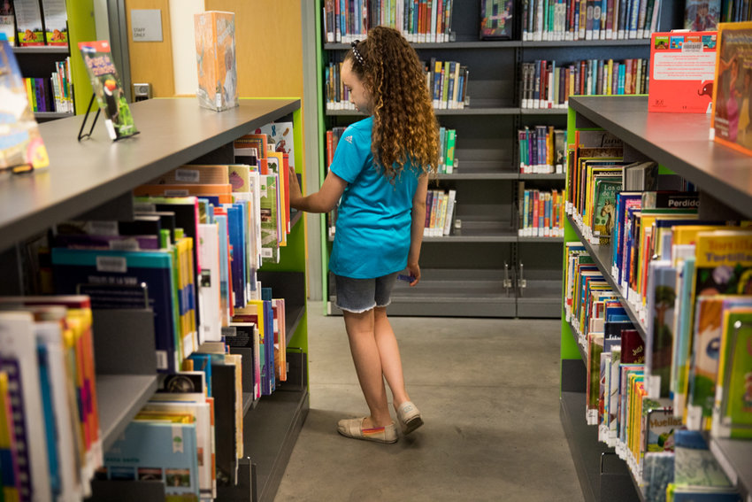 A young library patron browses selections in the children's section of the Kingsbridge Library. Like locations throughout the city, the Kingsbridge branch is bracing for the consequences of a proposed $10.4 million cut to library funding in next year's city budget.