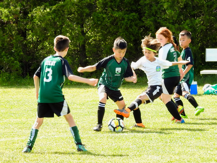 Riverdale Soccer Club Avengers' Ian Hahn, center, tries to work his way around a Park Slope defender as teammates Devin Cuddy (3), Sophie Chaifetz (7) and Jayden Jung (4) look on in the Avengers' 6-4 loss in the State Cup final.