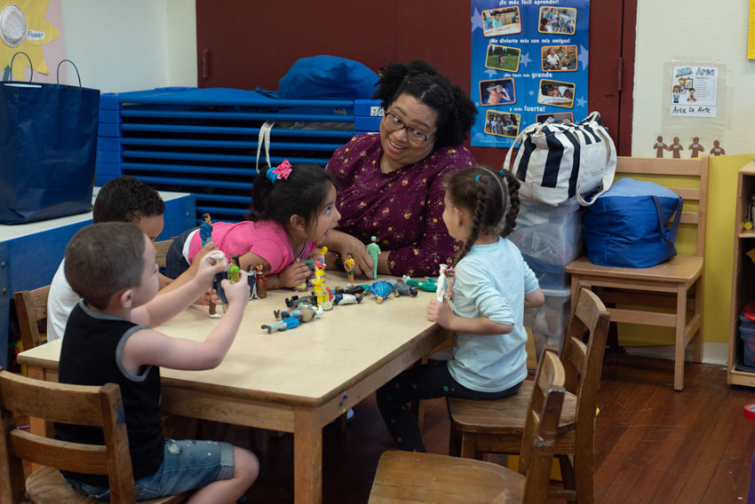 Pre-K students play with toys along with lead teacher Giovanni McKeiver at the Kingsbridge Heights Community Center. It's anything but fun and games for pre-kindergarten teachers at community-based organizations like KHCC, because within the context of the city's universal pre-K program, teachers at such organizations make 60 percent of their city-operated preschool counterparts.