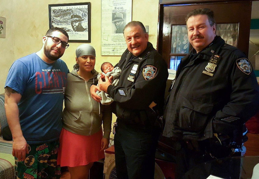 Officer Kevin Preiss, right, smiles with officer Roland Benson and the baby they helped deliver in January. Preiss reportedly died by suicide last month.