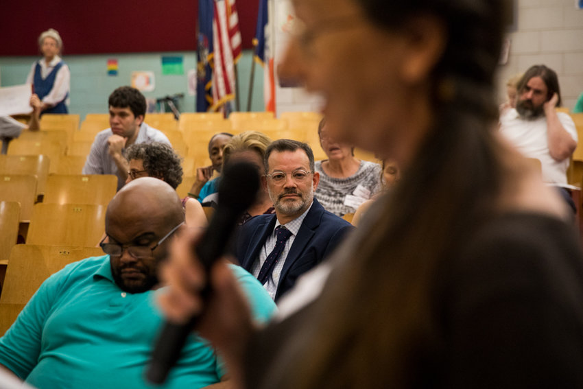 Councilman Andrew Cohen, center, listens as Jodie Colon reads a letter urging him to change his position on proposed changes to the Special Natural Area District during the June 27 Community Board 8 meeting. The board voted to overwhelmingly reject the process that would have instituted the greenbelt changes after learning Staten Island was removed from consideration.