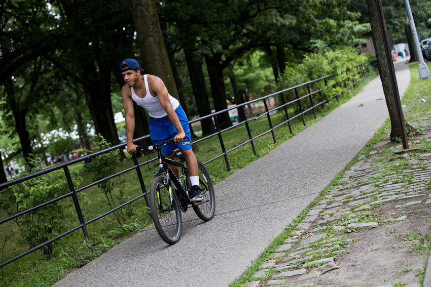 A cyclist rides on the sidewalk along Van Cortlandt Park in 2018. The U.S. Army Corps of Engineers and FEMA are building a 200-bed field hospital at the park that could begin accepting patients fighting the virus that causes COVID-19 later this month.