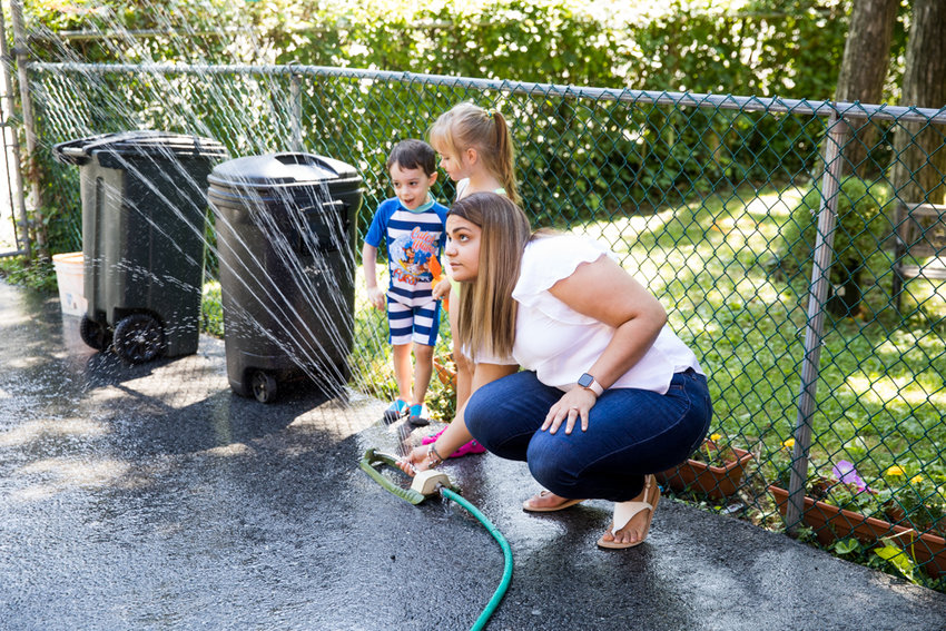 Wendy Nuñez, a teacher at Yearling Nursery School, adjusts a sprinkler for students to enjoy outside. Thanks to efforts by District Council 1707 Local 205 and the Day Care Council of New York, union members are due to get a long-requested pay increase.