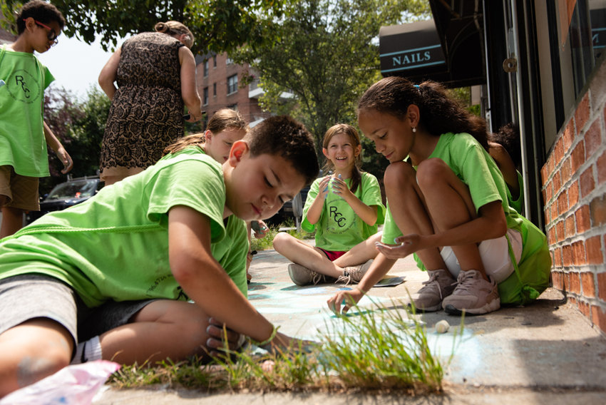 Rising sixth graders in Riverdale Community Center's summer program make chalk art on the sidewalk on West 236th Street outside Kingsbridge Riverdale Van Cortlandt Development Corp. They learned how to incorporate shapes and found objects into their chalky creations from artist Nina Seigenfeld.