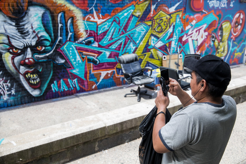 Kingsbridge resident Jose Zarate takes a picture of the graffiti mural on Summit Place. According to Zarate, the mural has changed at least three times in the last several weeks.