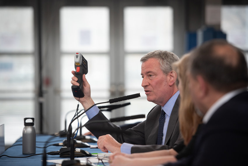 Mayor Bill de Blasio holds up an X-ray fluorescence analyzer as he announces lead-based paint testing at 135,000 NYCHA apartments during a news conference last April. The city's education department revealed that more than 900 classrooms have lead-based paint.