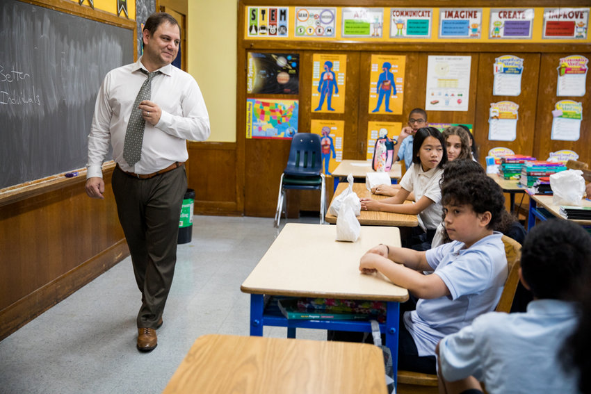 Paul Triantis, a seventh grade teacher at St. John's School, hears how his students spent their summer vacations during the first day of class this week. This is Triantis' first year teaching at the school.