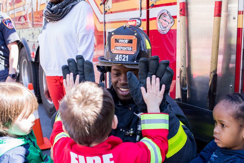 Ngonidzashe Musole, a firefighter with Engine 52, gives a double high-five to a student from Bedrock Preschool during a visit to the school last year. Engine 52 celebrates its 135th anniversary this year.