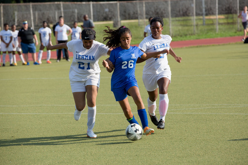 Riverdale/Kingsbridge Academy super sophomore Laura Lozano splits a pair of Lehman defenders on her way to scoring four goals and adding an assist in the Lady Tigers' 9-0 season-opening win.