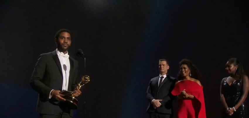 Jharrel Jerome accepts the Emmy for his role in the Netflix limited series 'When They See Us' while actors Peter Krause and Angela Bassett look on Sunday night.