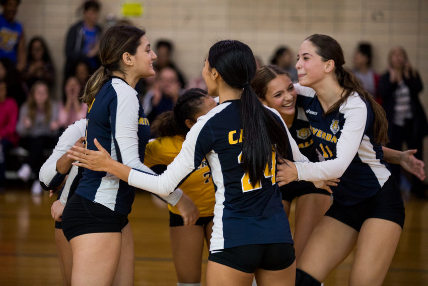 Patricia Casino (24), Adelina Elezaj (11) and other Riverdale/Kingsbridge Academy players celebrate during the Lady Tigers' straight-set victory over Roosevelt last Friday.