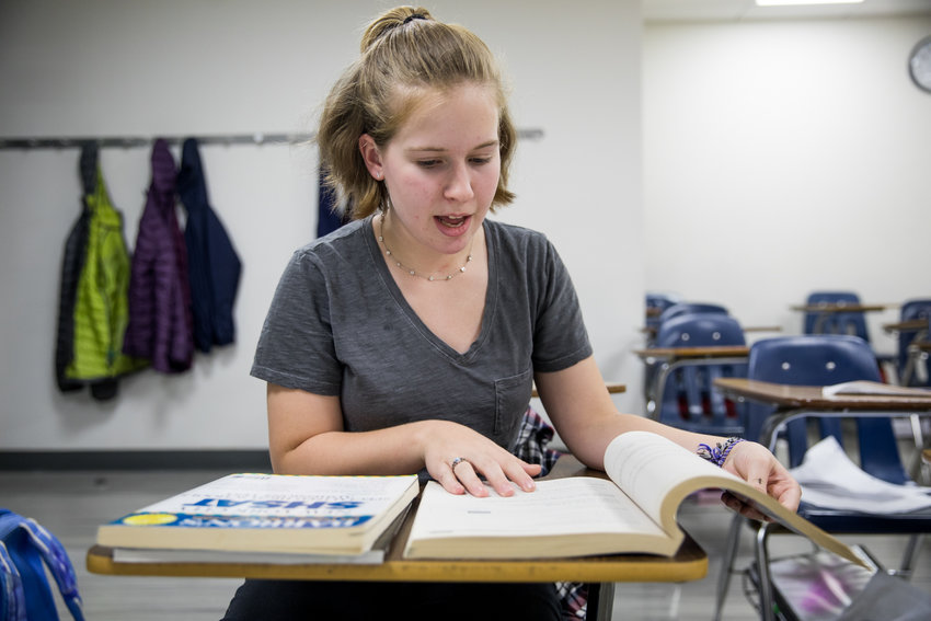 Kinneret Day School student Talia Schuldenrein looks through one of the test prep books she used to study for the Specialized High School Admissions Test, which she took along with thousands of other students Oct. 26. Talia hopes to get into Bronx Science where her father went to school.