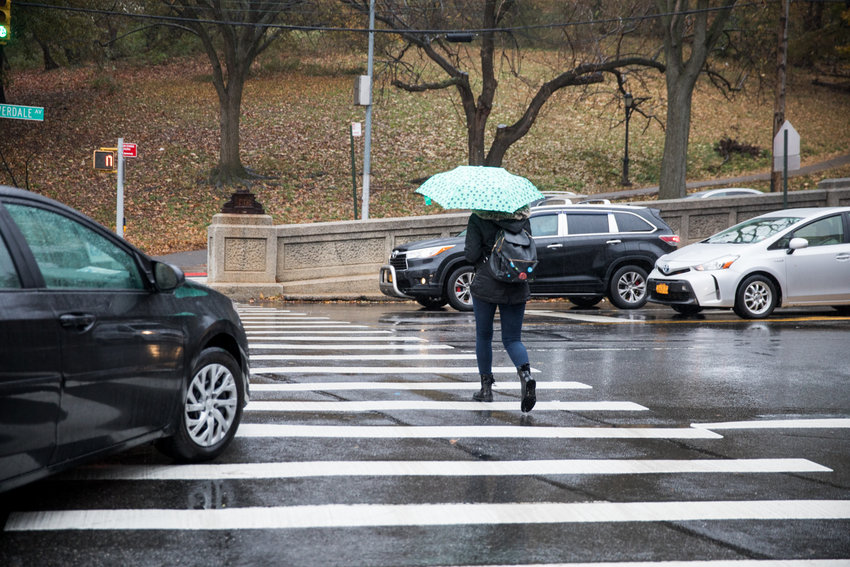 A pedestrian crosses Riverdale Avenue along the north side of the intersection with West 231st Street. A small phalanx of community members have circulated a petition calling for the removal of the northern crosswalk because it is a 'ticket trap' and can be unsafe for pedestrians.