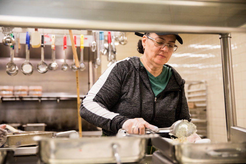Brenda Serrano serves food in the dining hall at Part of the Solution. Serrano first came to POTS seeking assistance herself in finding something to eat before she began volunteering there.