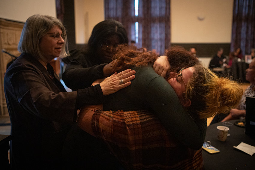 Kassandra Montes, center, hugs a family member after reading a poem dedicated to the memory of her deceased grandfather at a book launch for 'Our Words Have Power,' an anthology collection of poems written by Lehman College students. After reading the poem, Montes shared that she also was dedicating the book to her father, who died a week before the reading.