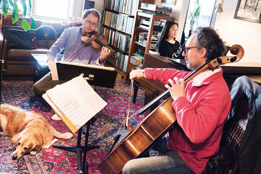 The di.vi.sion trio — Kurt Briggs on the violin, Renee Cometa-Briggs playing piano, and Matt Goeke on the cello — rehearse in an apartment in 2015. The group will perform at the Riverdale-Yonkers Society for Ethical Culture on Dec. 1.