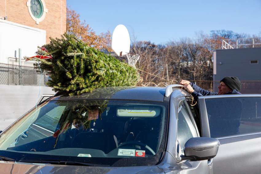 P.S. 81 parent association member Pete Kelly ties a tree to the roof of the Bonilla family's car during the association's annual Winter Fest. The PA's fundraisers help kickstart extra programs at the school.