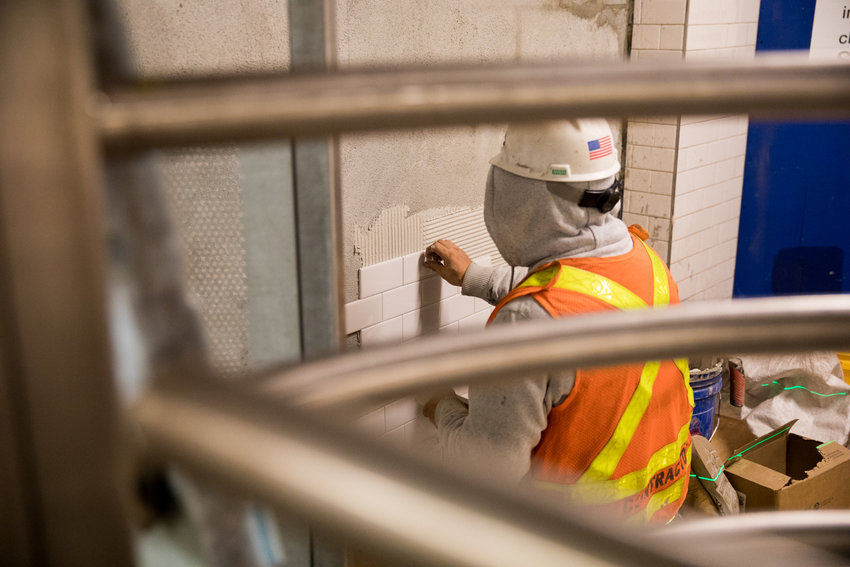 A construction worker tiles a wall in the 168th Street subway station near the sectioned-off passageway leading to the elevators that will soon take passengers to the 1 train platform once again. The elevators and the platform have been closed for nearly a year for much-needed renovations.