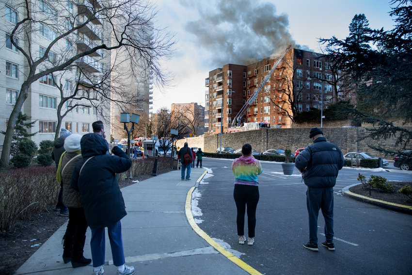 Community members watch as firefighters work to extinguish a three-alarm fire at 601 Kappock St.