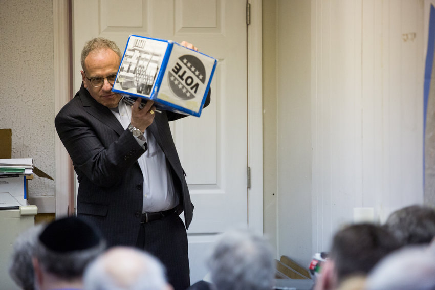 Assemblyman Jeffrey Dinowitz shakes a ballot box at a Jan. 15 endorsement meeting of the Benjamin Franklin Reform Democratic Club. The state lawmaker has tremendous influence on one of the borough's oldest and biggest political clubs, but said he did not retaliate against state Sen. Gustavo Rivera for his backing of a leadership change at the club.