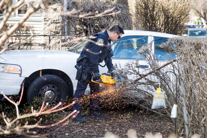 A police officer cuts away part of a wire mesh fence outside 400 W. 261st St., where a car crashed through the fence on the morning of Feb. 27,