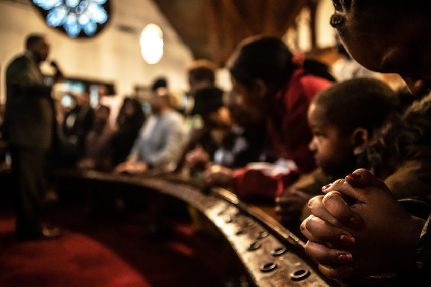 Parishioners kneel for a blessing from guest pastor David Anthony Gilmore at St. Stephen's United Methodist Church during a Feb. 23 service marking the congregation's 195th anniversary.