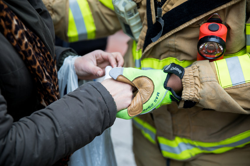 A resident of 215 W. 242nd St., where a one-alarm fire broke out Friday morning, gets her hand bandaged by emergency personnel. The fire injured 11 people, four critically and seven non-critically.