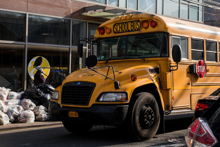 A school bus picks up students from Amber Charter School on Corlear Avenue. The school plans to end bus service this June, a change some parents aren't happy about.