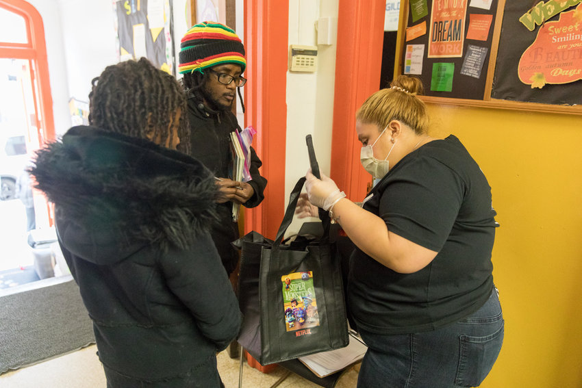 P.S. 207 aide Amy Jimenez hands bags of learning materials to Frederick Hay, the parent of three children enrolled at the Godwin Terrace school, soon after Gov. Andrew Cuomo shut down public schools in the state last month. Whether schools reopen this academic year is up for debate as Mayor Bill de Blasio has said definitively no, while Cuomo is still waiting to see what happens in the coming weeks.