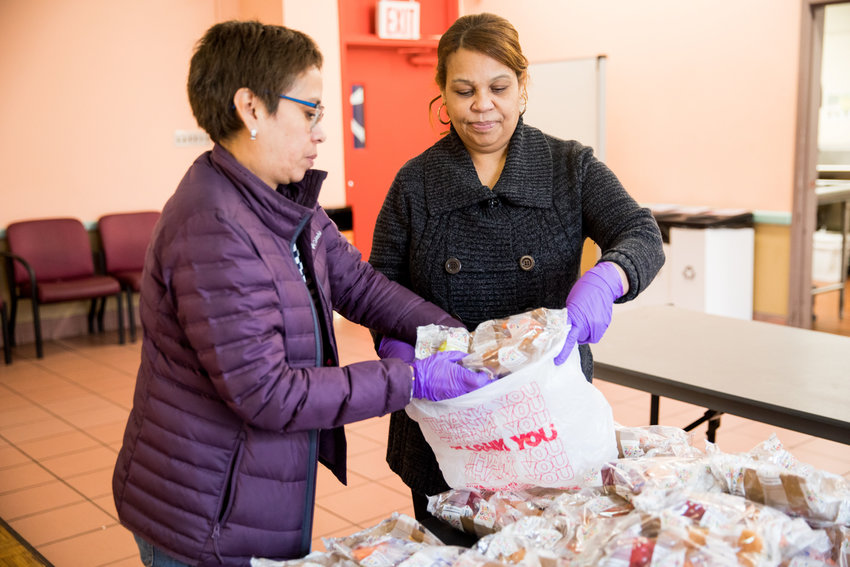 Norma Collado, left, and Carmen Morel pack food for a neighbor at the Kingsbridge Heights Community Center. The organization partnered with celebrity chef Jose Andres' World Central Kitchen to serve as a food distribution center in the neighborhood. KHCC has moved quickly to adapt its services to meet the needs of the community during the coronavirus pandemic.
