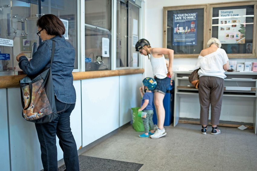 Customers take care of their postal needs at the post office on West 238th Street in Summer 2018. More recently, customers have complained about not receiving mail, primarily because this particular location is shut down because of the coronavirus pandemic.