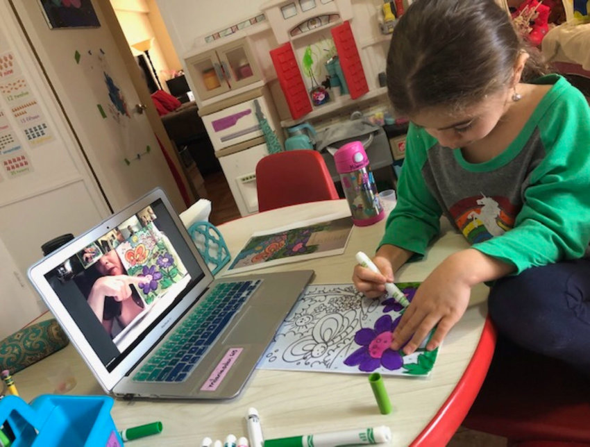 Milania Ellin uses markers to color in a garden scene during a weekly art class led by Cathy Sanacore on the video conferencing program Zoom.