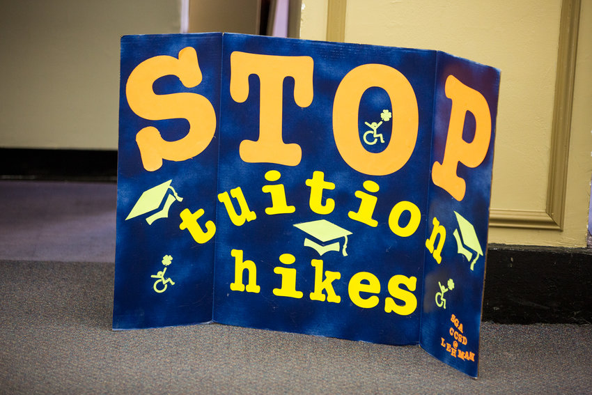 A poster that reads 'Stop tuition hikes' stands on the floor during a March 9 forum hosted by the CUNY Rising Alliance at Lehman College, which dealt with proposed budget cuts and tuition hikes.