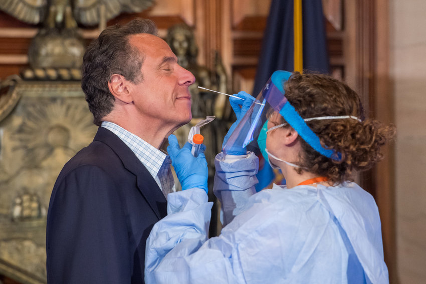 Dr. Elizabeth Dufort conducts a swab diagnostic test of Gov. Andrew Cuomo, looking to see if he has the virus that causes COVID-19. The test was part of a live demonstration Sunday during the governor's daily coronavirus media briefing.